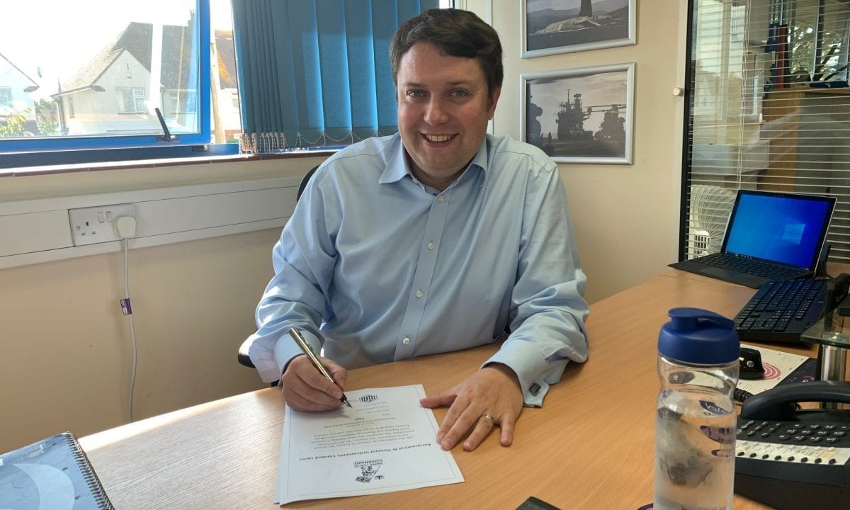 AGI Managing Director officially signing Armed Forces Covenant document